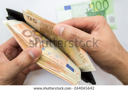 close up of male hands taking out money from the wallet - stock photo