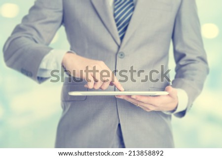 Close-up of male hands touching digital tablet, formal businessman standing with blur background. - stock photo