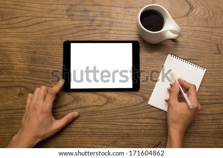 Close-up of male hands using a digital tablet and writing notes with a cup of coffee - stock photo