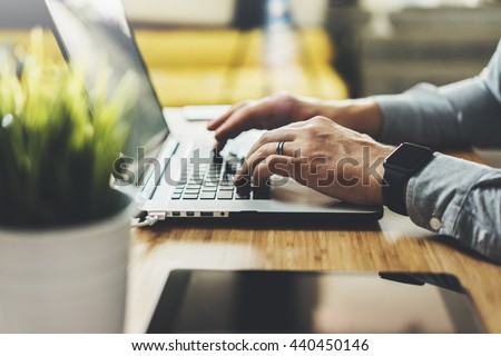 Close-up of male hands using modern laptop in home interior, young hipster man wearing generic design smart watch and working at his office via portable computer, film effects, flare light - stock photo