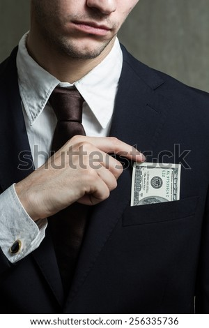 Close up of male hands with money. Puts money in your pocket - stock photo