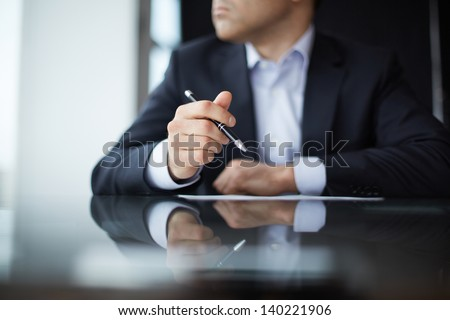 Close-up of male hands with pen - stock photo