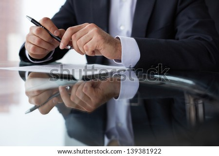 Close-up of male hands with pen over document - stock photo