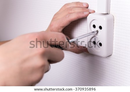 close up of male hands with screwdriver installing electrical socket on wall - stock photo