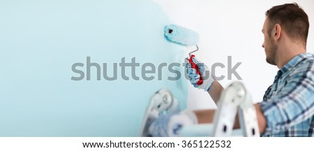 close up of male in gloves holding painting roller - stock photo