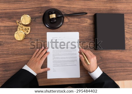 Close-up Of Male Judge Reading Paper In Courtroom - stock photo