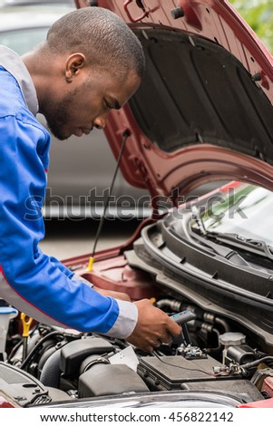 Close-up Of Male Mechanic Checking Car Battery Level With Multimeter - stock photo