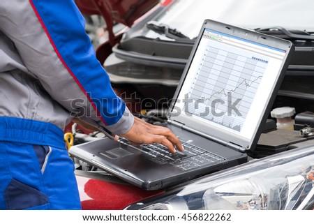 Close-up Of Male Mechanic Using Laptop For Examining Car Engine - stock photo