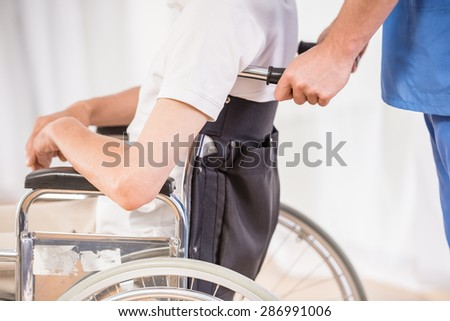 Close-up of male nurse taking care about senior patient in wheelchair at clinic.