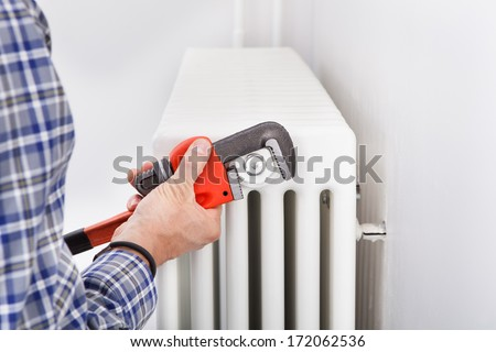Close-up Of Male Plumber Fixing Radiator With Wrench - stock photo