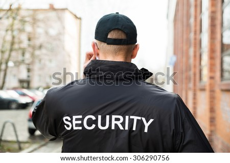 Close-up Of Male Security Guard Wearing Black Jacket - stock photo