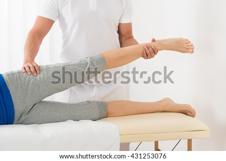 Close-up Of Male Therapist Giving Leg Massage To Woman