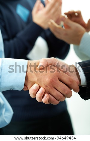 Close-up of males handshaking with applauding people on background