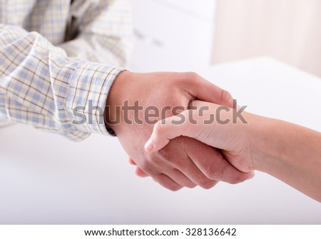 Close up of man and woman shaking hands at white desk