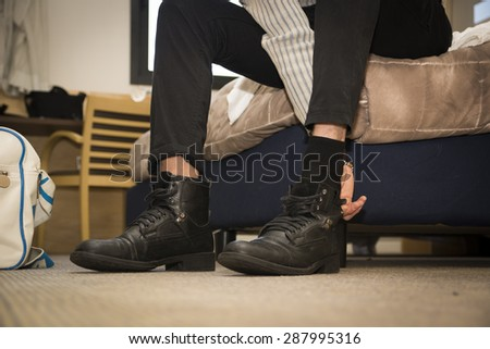 Close-up of man at home putting on shoes. View of his feet on the bedroom floor
