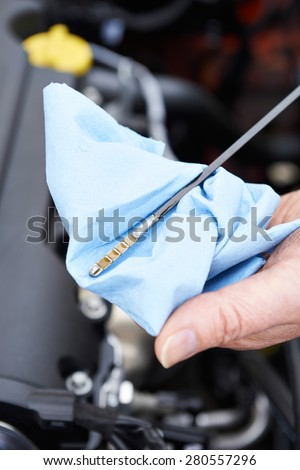 Close-Up Of Man Checking Car Engine Oil Level On Dipstick - stock photo