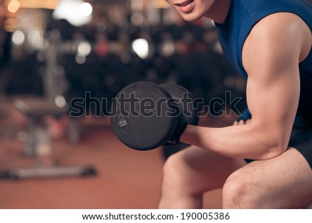 Close-up of man exercising with dumbbell - stock photo