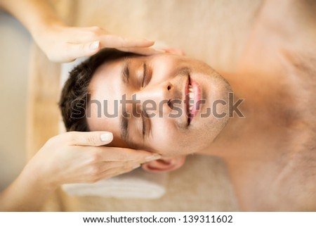 close up of man face in spa salon getting facial massage - stock photo