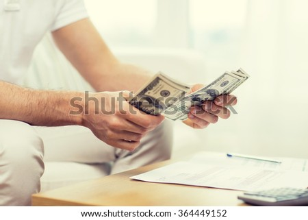 close up of man hands counting money at home - stock photo
