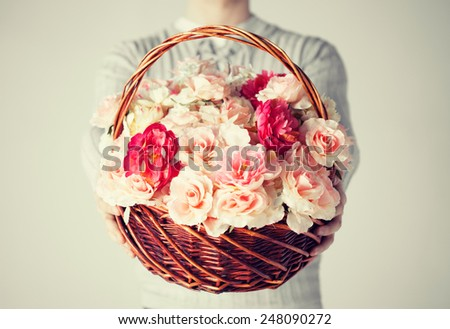 close up of man holding basket full of flowers. - stock photo