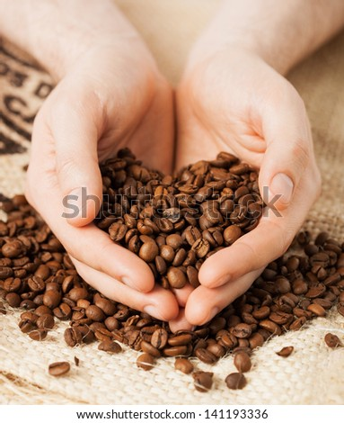 close up of man holding coffee beans - stock photo