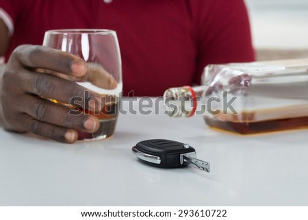 Close-up Of Man Holding Glass Of Whisky With Car Key On Table - stock photo