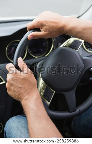Close up of man holding his wheel in his car - stock photo
