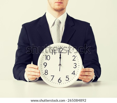 close up of man holding wall clock - stock photo