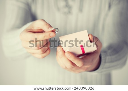 close up of man holding wedding ring and gift box. - stock photo