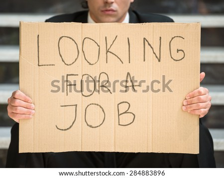 Close-up of man in suit sitting at stairs with sign in hands. Unemployed man looking for job. - stock photo
