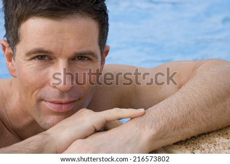 Close up of man leaning on edge of swimming pool - stock photo
