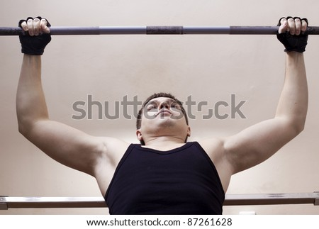 Close-up of man lifting  metal weight - stock photo