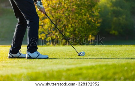 Close-up of man playing golf on green golf course. Hitting golf ball - stock photo