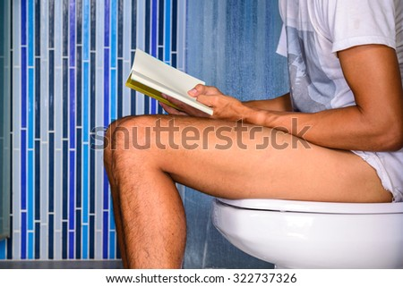 Close up of man reading a book while defecating in private toilet. - stock photo
