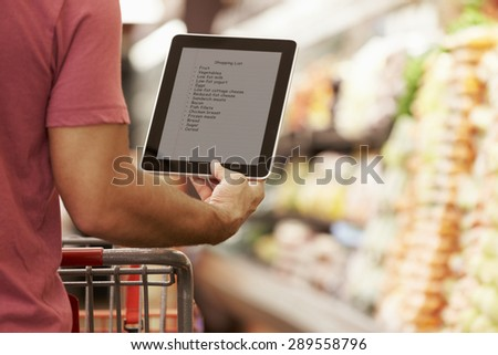 Close Up Of Man Reading Shopping List From Digital Tablet In Supermarket - stock photo