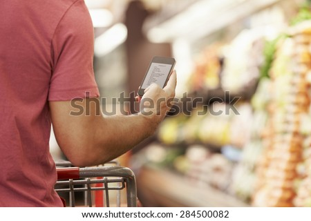 Close Up Of Man Reading Shopping List From Mobile Phone In Supermarket - stock photo