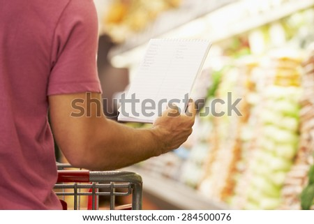 Close Up Of Man Reading Shopping List In Supermarket - stock photo