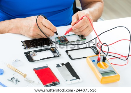 Close-up Of Man Repairing Cellphone With Multimeter - stock photo