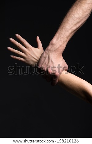 Close up of man's and woman's hands. Isoleted on black
