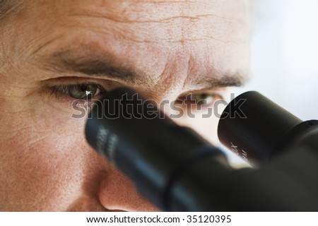 close up of man's eyes looking through microscope - stock photo
