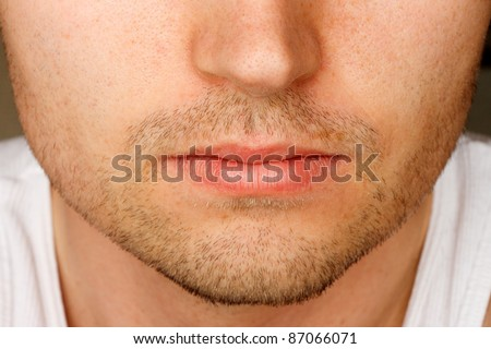 Close up of man's face sporting a 5 o'clock shadow - stock photo