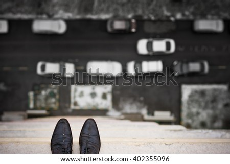 Close-up of man's feet standing on the edge of the roof. Top view on man's boots on the balcony of high building. Depression and instability concept. Crisis. - stock photo