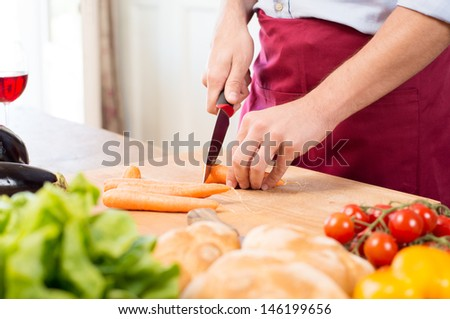 Close-up Of Man's Hand Cutting Carrots