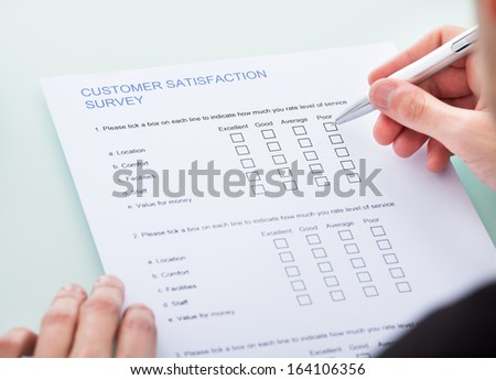 Close-up Of Man's Hand Filling Customer Survey Form - stock photo