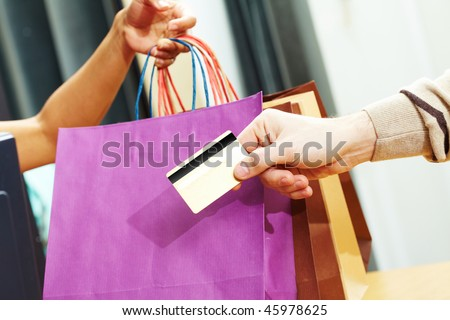 Close-up of man?s hand passing over credit card to shop assistant after shopping - stock photo