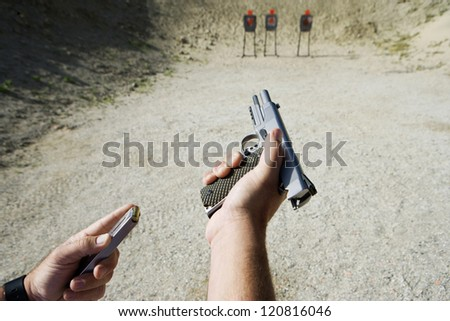 Close up of man's hand reloading gun - stock photo