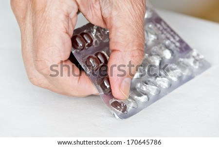 Close up of man's hand taking out pills from blister - stock photo