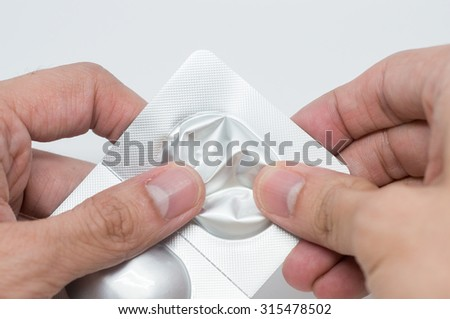 Close up of man's hand taking out pills from blister pack - stock photo