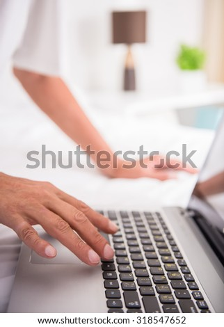Close up of man's hands is using laptop.