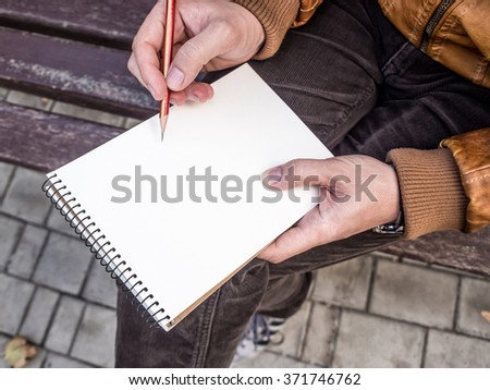 Close up of man's hands with pencil writing on notebook mockup - stock photo
